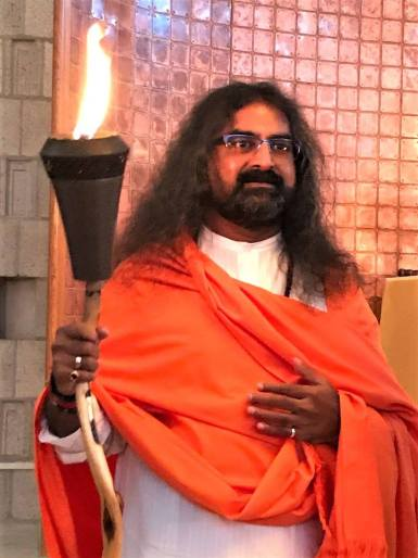Mohanji holding the lamp of love, peace and truth.